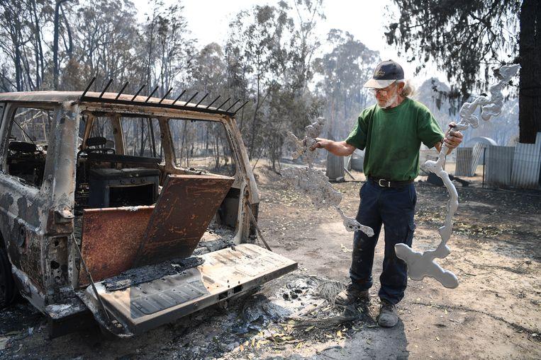 Met enkele gesmolten aluminiumresten in zijn handen bekijkt een man zijn uitgebrande auto. Beeld EPA