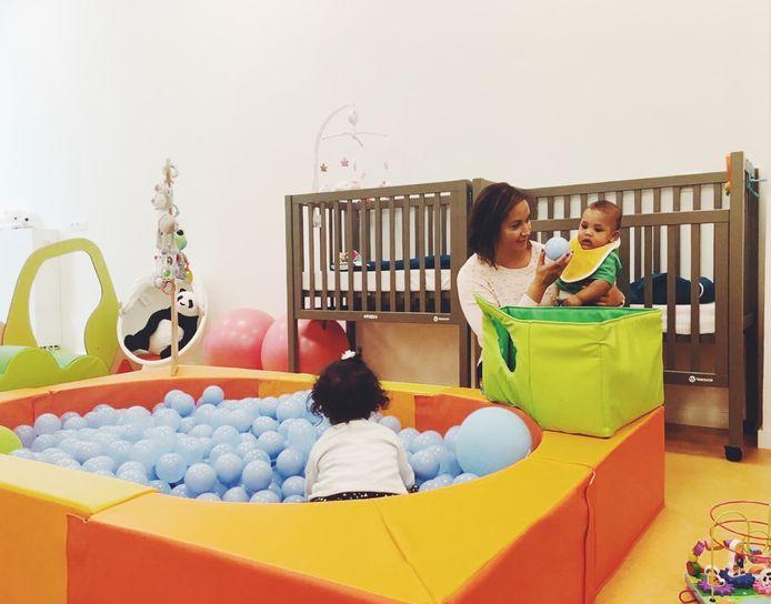 Schepen Nabilla Ait Daoud (N-VA) ontfermt zich over een baby in een kinderdagverblijf. Dit beeld dateert van voor de coronapandemie.