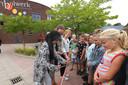 Wethouder Bouke de Bruin knipt met leerlingen het lint door waarmee het blauw-groenen speeltuin officieel is geopend.