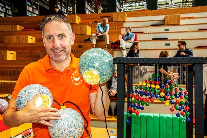 Rolph Adriaansen naast zijn ontwerp en met zijn plastic ballen; 169 vormen de uiteindelijke kroonluchter013.