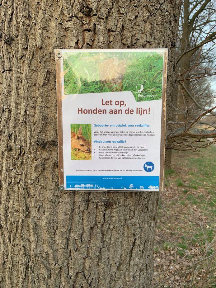 Door middel van posters worden mensen verzocht  hun hond aan te lijnen.