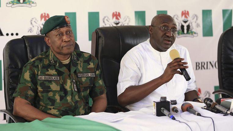 Mike Omeri (rechts), de coördinator van het Nationaal Informatiecentrum en Chris Olukolade (links), woordvoerder van het leger, spreken de pers toe na een reeks aanslagen in Nigeria. Beeld reuters