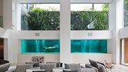 In deze flat zie je het zwembad door een glazen muur in de living