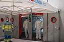 Artsen en verpleegkundigen wachten op de volgende patiënt bij een inderhaast ingericht noodhospitaal in Madrid. Het snel stijgende aantal besmettingen dreigt de gezondheidszorg in Spanje te veel te worden.