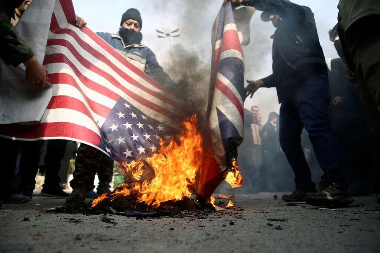 Iraanse demonstranten steken Amerikaanse en Britse vlaggen in brand. Beeld VIA REUTERS