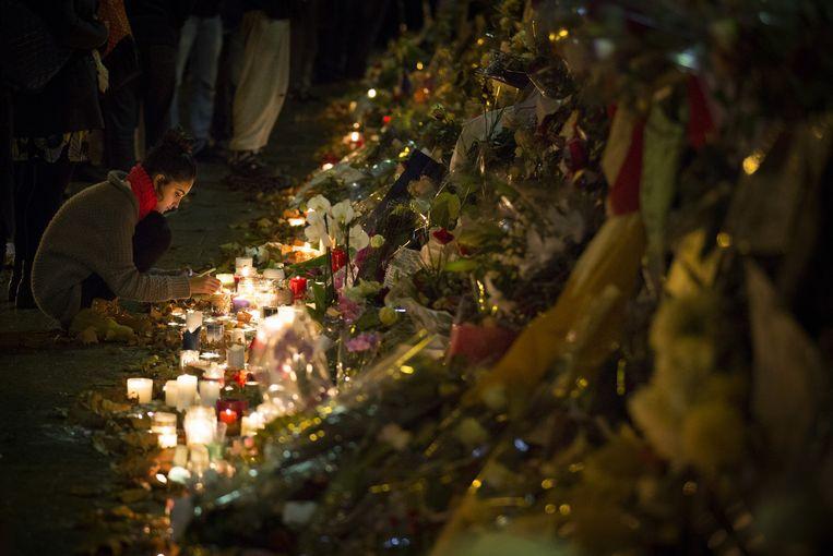 Een vrouw steekt een kaars aan voor de slachtoffers in Parijs. Beeld anp