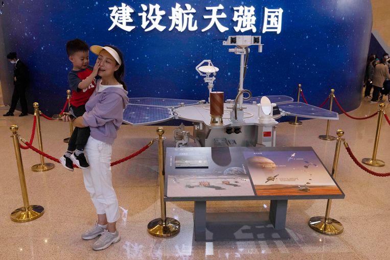 Bezoekers poseren bij een model van de Chinese Mars-rover Zhurong in het Nationaal Museum van Peking. Beeld AP