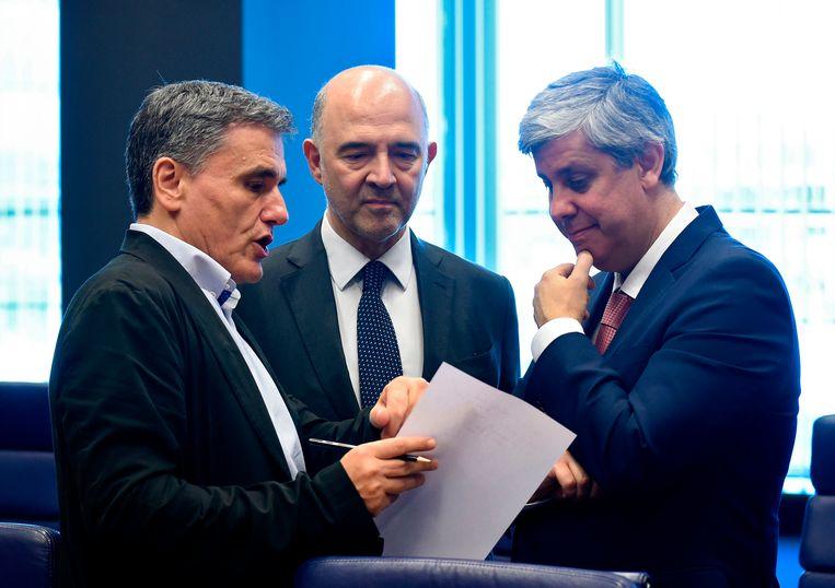 De Griekse minister van Financiën Euclid Tsakalotos (l.), de Europese Commissaris Pierre Moscovici (m.) en de Portugese minister van Financiën en Eurogroepvoorzitter Mario Centeno (r.). Beeld AFP