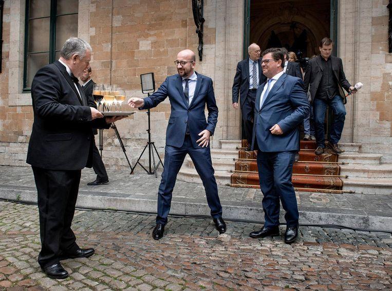Premier Michel en minister Bart Tommelein komen als eersten buiten voor de receptie. 11 juli viering stadhuis Brussel. Beeld Eric de Mildt