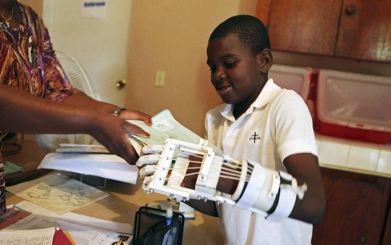 Binnen een paar jaar bijna gewoon gewoon geworden: de 3D printer. Een model ontwerpen op de computer en daar een fysiek opject van printen kan al thuis, en voor talloze toepassingen wordt de 3D-printer al gebruikt. <br /><br />Hier: de gehandicapte Stevenson Joseph (12) uit Haïti leert om een prothetische hand uit de 3D-printer te gebruiken. Hij is de eerste Haïtiaan die een prothese uit de printer krijgt. Beeld reuters