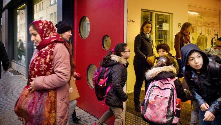 School de 'Vier Winden' in Molenbeek opende woensdag terug haar deuren. Weliswaar nog onder toezicht van de patrouillerende politie. Beeld Eric de Mildt