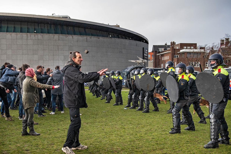 De ene demonstrant op het Museumplein in Amsterdam gebaart de politie het rustig aan te doen, een ander gooit een zware steen.   Beeld Guus Dubbelman / de Volkskrant