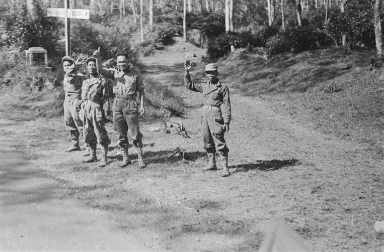 [Bij een driesprong groeten vier KNIL militairen het convooi] [Verkeersbord wijst naar Bandoeng en terug naar Bogor. 1946 Beeld Nationaal Archief