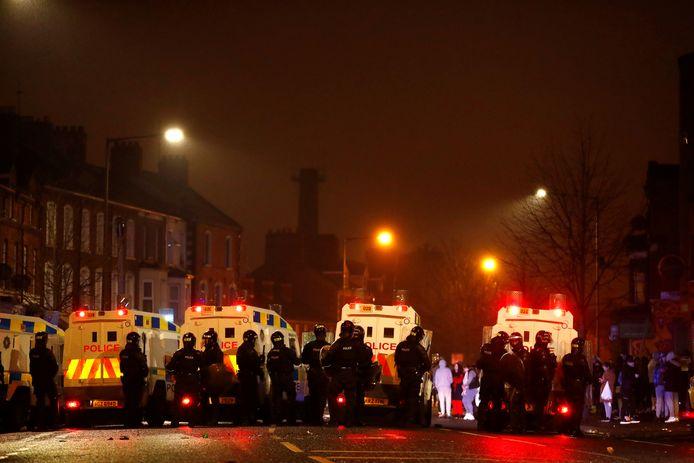 Politiemensen staan bij hun voertuigen in Belfast.