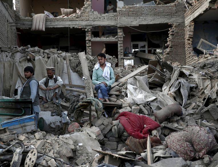 Mensen zitten op de resten van hun bezittingen na de aanslagen van gisteren.