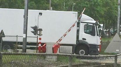 Vrachtwagenchauffeur negeert spoorwegalarm en komt vast te zitten onder bareel