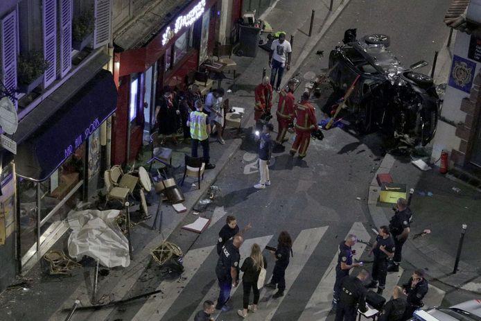 """Des pompiers travaillent tandis que des policiers français surveillent une rue après qu'une voiture a foncé sur la terrasse du café """"Bar aux sports"""", au croisement des rues Sauffroy et Guy Moquet, dans le nord-ouest de Paris, le 29 juillet 2021."""