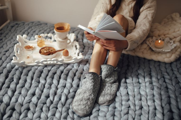 Woman with long hair drinking hot coffee and reading book in bed. Woman in woolen socks and sweater sitting on wool chunky merino plaid. Cozy winter morning concept. Beeld Getty Images