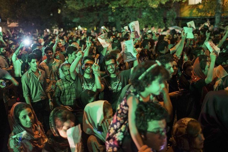 Aanhangers van Rohani vieren zijn overwinning op straat in Teheran, zaterdagavond. Beeld reuters