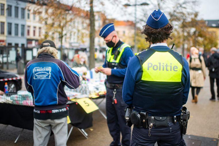 Antwerpse agenten controleren of mensen hun mondmasker dragen. Beeld Klaas De Scheirder