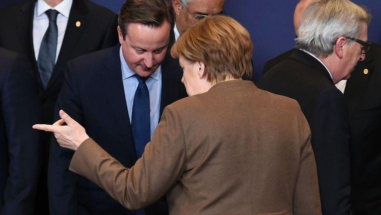 De Britse premier David Cameron en de Duitse bondskanselier Angela Merkel praten in Brussel. Beeld afp
