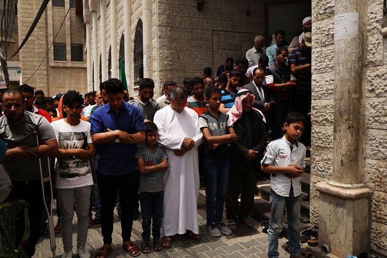 Mannen bidden om Mustafa, een veertigjarige vader die vijf kinderen nalaat en gisteren gedood werd in de protesten aan de grens met Israël. Beeld Getty Images