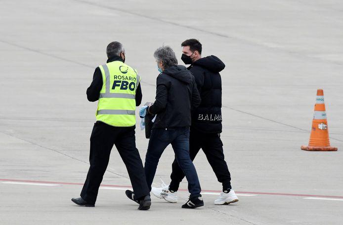 Messi en vader Jorge op de luchthaven van Rosario.