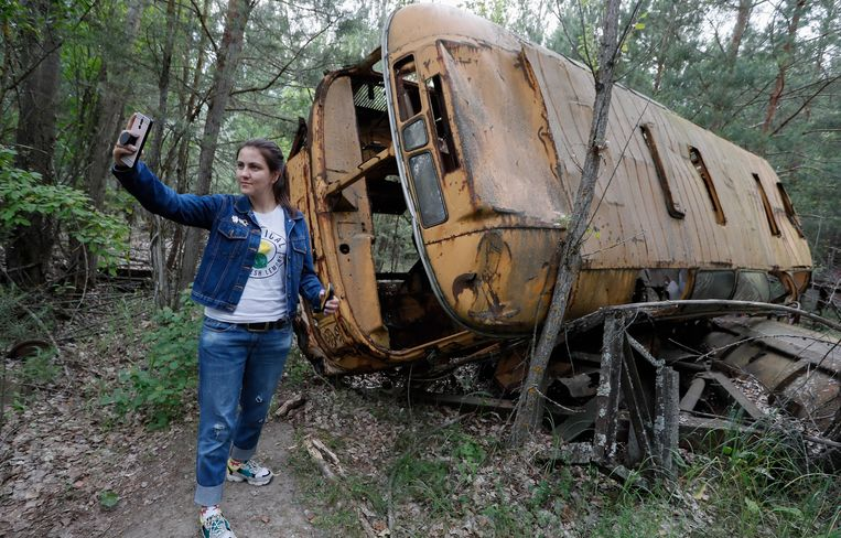 Een bezoeker maakt een selfie bij een verlaten bus tijdens een rondleiding in de exclusion zone.  Beeld EPA