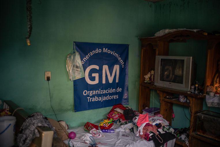 De kleine woning van Israel Cervantes, bezaaid met kleren en speelgoed.Aan de muur hangt de vlag van de onafhankelijke vakbond Generando Movimiento, die vooralsnog geen vuist kan maken. Beeld Volkskrant