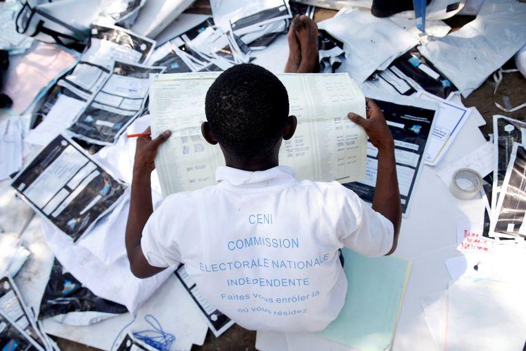 Een man bekijkt kiesmateriaal in Kinshasa op de eerste dag van het nieuwe jaar. Beeld REUTERS
