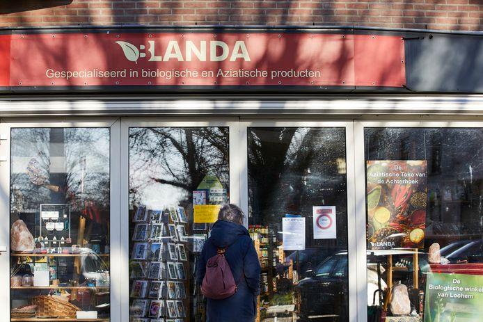 Een voorbijganger staat voor de gesloten deuren van de door de burgemeester gesloten winkel Blanda.