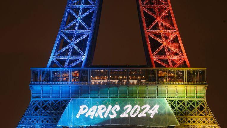 De organisatoren lieten de officiële slogan 'Made for Sharing' in de olympische kleuren afbeelden op de Eiffeltoren. Beeld Getty Images