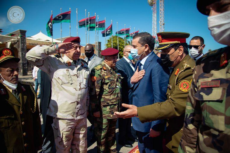 De Libische premier Abdelhamid Dbeibah wordt verwelkomd bij aankomst in Tripoli. De steenrijke zakenman wacht een zware missie.  Beeld Reuters