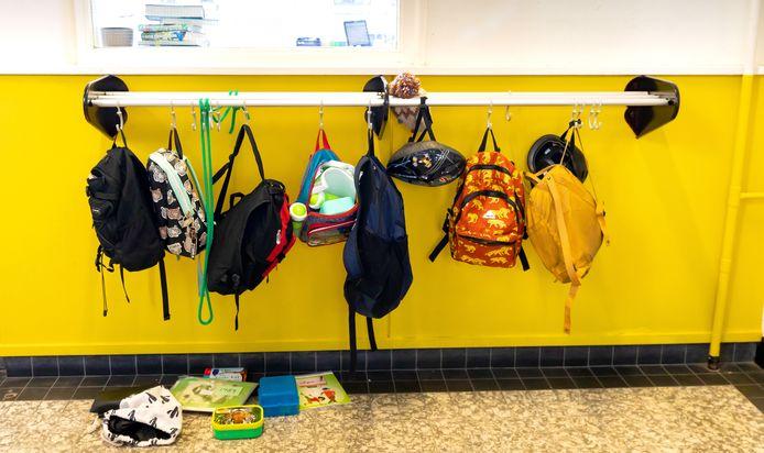 Tassen aan de kapstok in de gang van een school. Vanaf komende week weer een vertrouwd beeld.