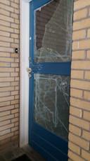 De provisorisch herstelde deur aan de Gombertstraat laat zien hoe de politie vorig jaar met grof geweld de woning van K. binnenviel.