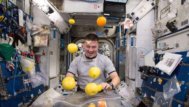 Een astronaut in het ISS opent een zak vers fruit Beeld AFP