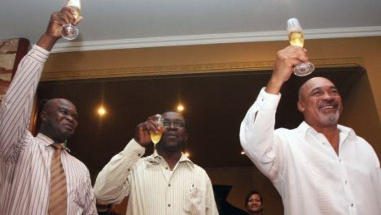 Ex-legerleider en voorzitter van de Mega Combinatie, Desi Bouterse (R), en ex-rebellenleider tevens voorzitter van de A-Combinatie, Ronnie Brunswijk, heffen het glas na de ondertekening van het samenwerkingsprotocol tussen de beide partijen op donderdag 3 juni 2010 in Pararmaribo. In het midden Caprino Allendy, plaatsvervangend voorzitter van het Surinaamse parlement. Foto ANP Beeld