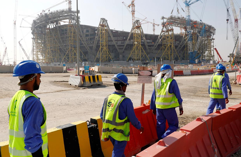 Arbeiders op weg naar het Lusail-stadion in Doha, waar in 2022 de finale van het WK voetbal wordt gespeeld. Beeld REUTERS