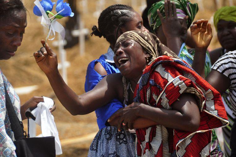 Nabestaanden tijdens de begrafenis van een ebola-slachtoffer in Monrovia, Liberia. Beeld ap