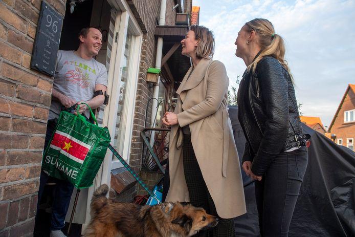 Vrijwilligers Fela (midden) en Suus brengen boodschappen bij Daniël die de deur niet uit kan.