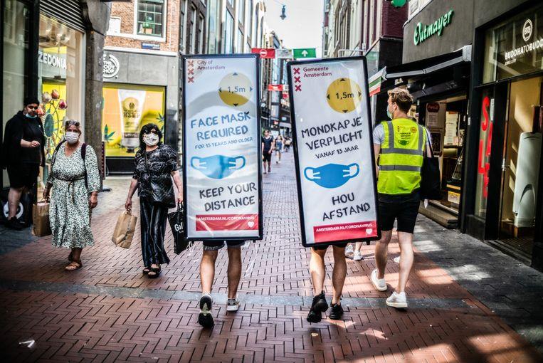 Werknemers met grote waarschuwingsborden op hun rug lopen door de Kalverstraat. Beeld Joris van Gennip