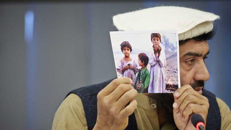 De Pakistaanse activist Karim Khan toont een foto van slachtoffers tijdens zijn pleidooi in de Tweede Kamer tegen Amerikaanse aanvallen met drones. Beeld anp