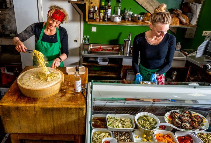 Eigenaresse van Mangiare, Aggy Kan (links), roert en flambeert de pasta parmagiano.