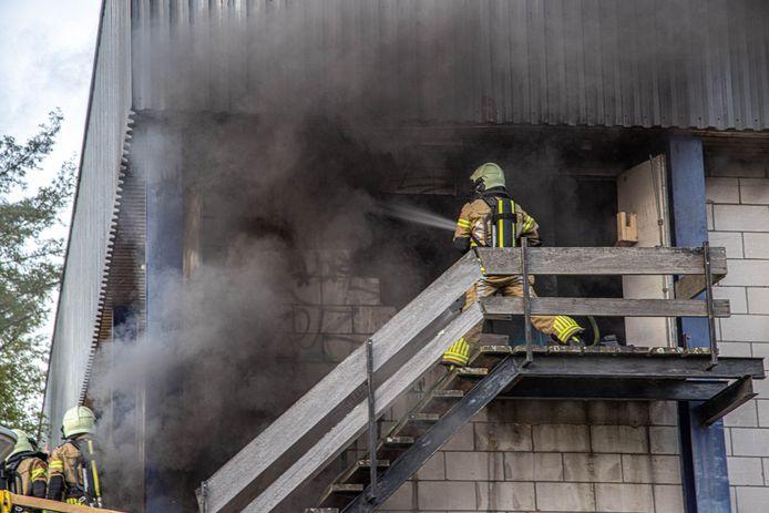 De brandweer bestrijdt het vuur nadat een deel van de muur op de bovenverdieping is weggebroken.