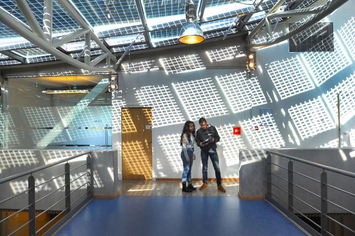 ICT-studenten Hasina Noori en Kylian Lauer overleggen in de hal van het HZ-gebouw in Middelburg.