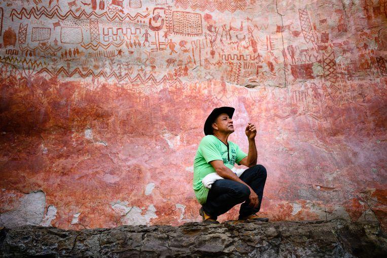 Jose Noe Rojas zit bij de rotsschilderingen van Cerro Azul in de Colombiaanse Amazone. De voormalige cocaboer heeft het zijn levenswerk gemaakt de schilderingen te beschermen.  Beeld Getty