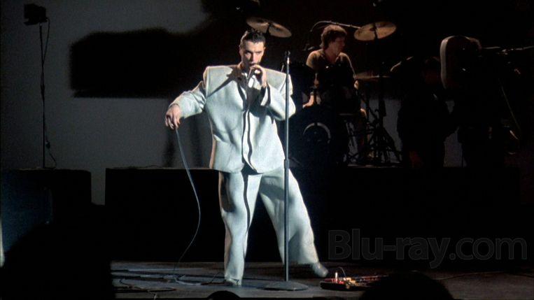 In Stop Making Sense droeg Byrne een overmaats pak, dat zijn vreemde dansbewegingen uitvergrootte en reusachtige schaduwen wierp.  Beeld