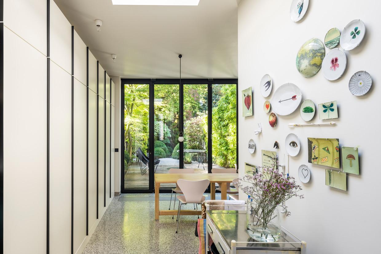 Een muur in de keuken wordt volledig bedekt met kasten, de andere is bekleed met bordjes uit New York, Parijs, Puglia en Portugal.  Beeld Luc Roymans