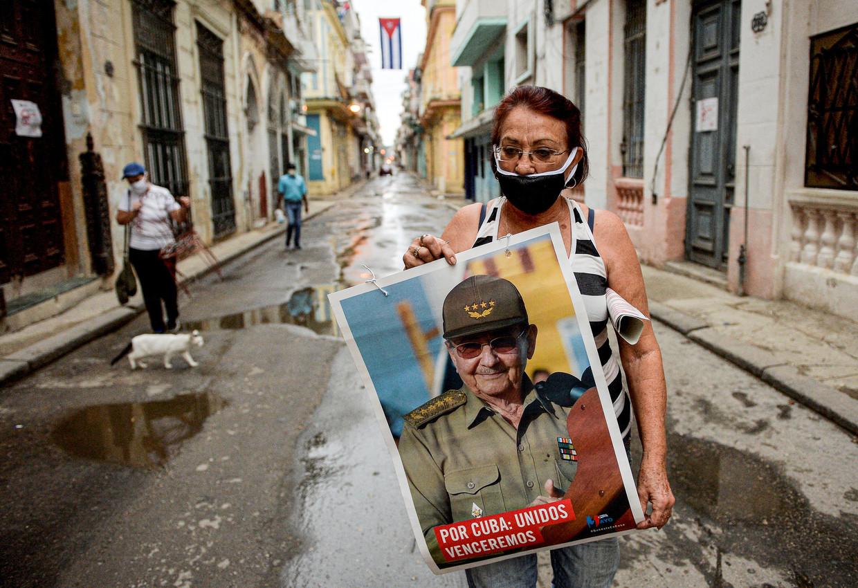 De voorzitter van het 'comité voor de verdediging van de revolutie' Marta Parra draagt een afbeelding van Raúl Castro ter ere van de dag van de arbeid. Beeld AFP