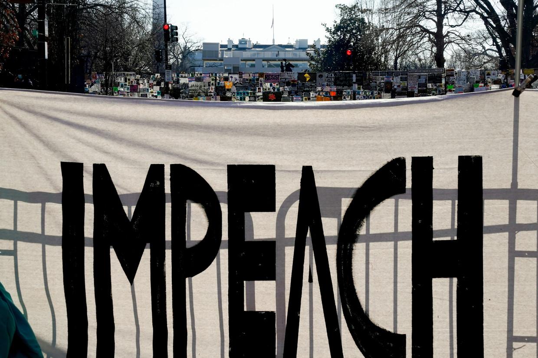 Een spandoek aan het Witte Huis roept op tot een impeachment van Trump. Beeld REUTERS